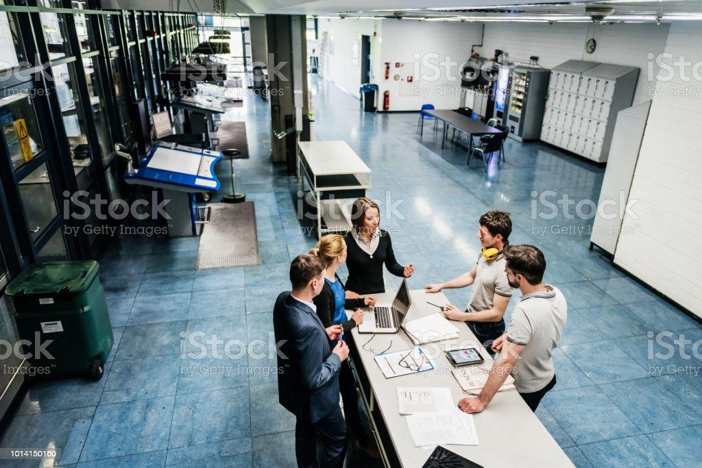 Meeting Between Engineers On Factory Floor A meeting between a group of engineers at a table on a printing factory floor. Adult Stock Photo