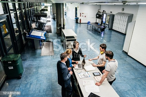 A meeting between a group of engineers at a table on a printing factory floor.