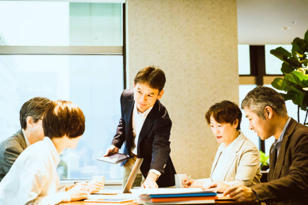Meeting held in an open office Japanese men and women gather around wooden tables and are doing business meetings using laptops and tablet terminals. A male is doing a presentation. only japanese stock pictures, royalty-free photos & images