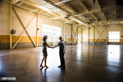 Businessmen an businesswoman meeting in empty warehouse.