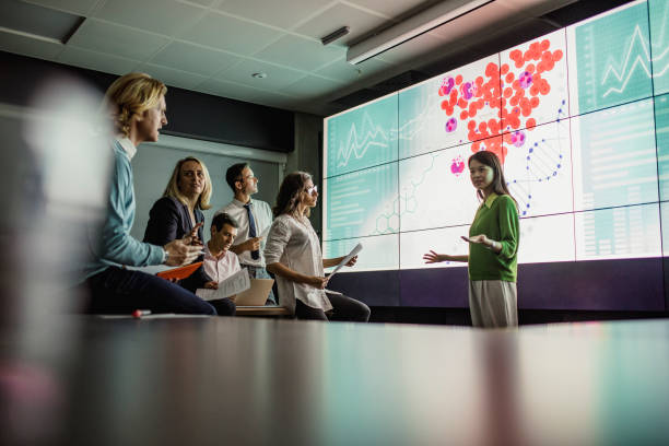 Meeting in Front of a Large Display Screen stock photo
