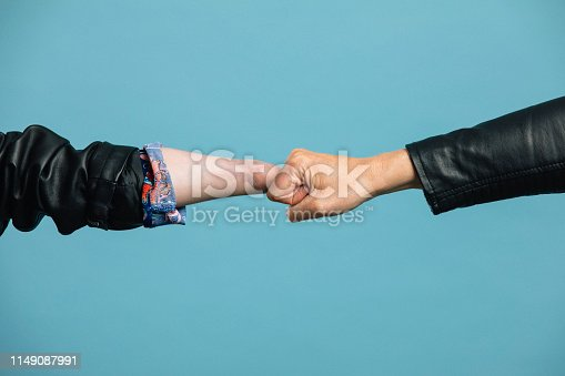 A human hand and a robotic hand, meeting in the middle and touching knuckles.