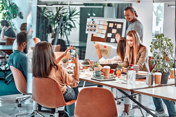 Meeting in the office, productive team of young professionals working at a large table using modern technology devices. stock photo