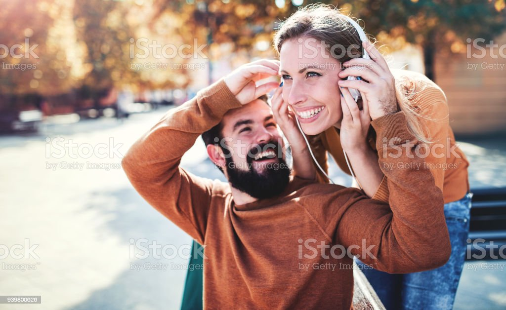 Meeting in the park. Couple in love listening to music with headphones. Love, dating, romance stock photo