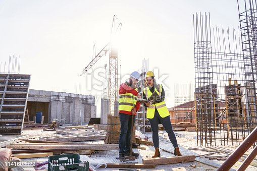 A Teamwork of an Architect - Project Manager and a Construction worker at site of a reinforced concrete building, checking the Progress of the Building Activity.