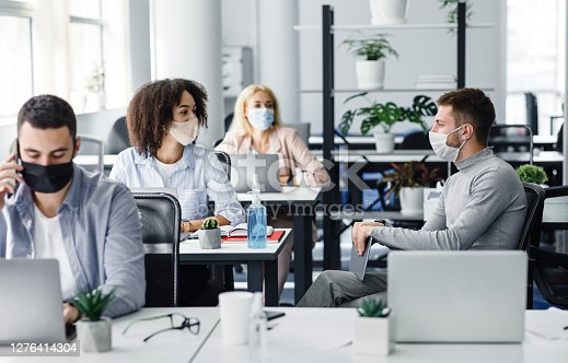 Meeting of colleagues in coworking office during coronavirus epidemic. Multiracial workers of modern company in protective masks discussing work issues at workplaces with gadgets and antiseptics, free space