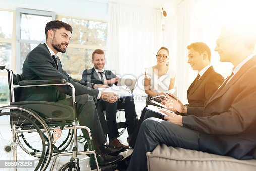 istock Meeting of disabled people in a bright room with wide windows. Men in wheelchairs businessmen. 898073298