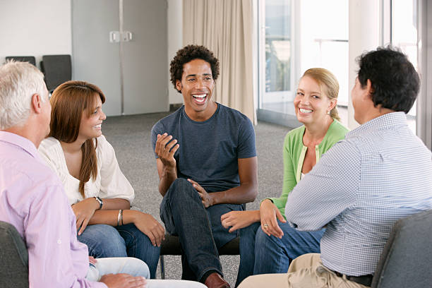 Meeting Of Support Group Meeting Of Support Group Smiling And Laughing. group therapy stock pictures, royalty-free photos & images