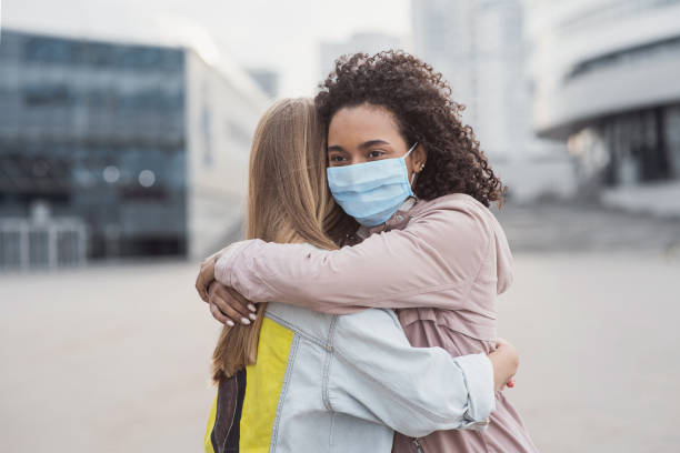 Meeting of two happy friends hugging in the street wearing protective face mask stock photo