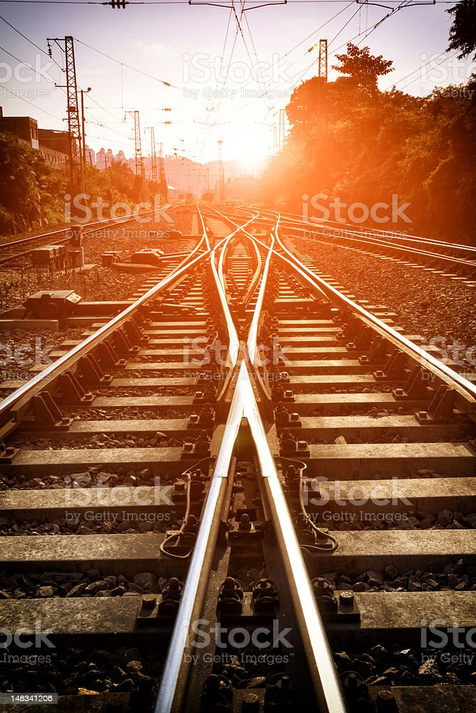 Meeting of two railroads with sunset background royalty-free stock photo