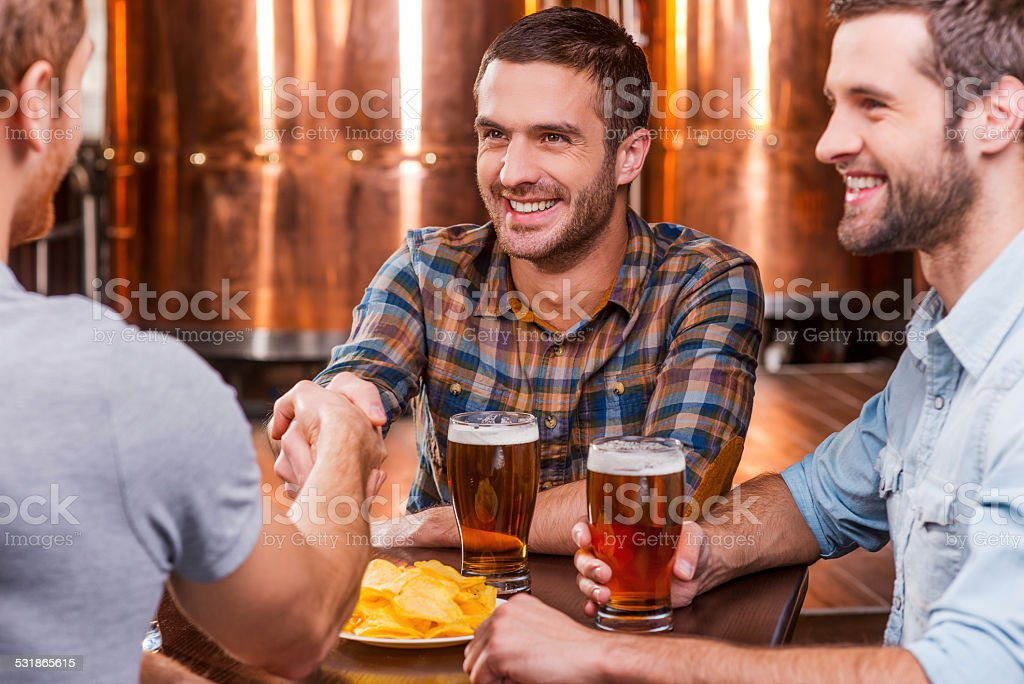 Meeting old friends. Three happy young men sitting in beer pub together while two of them handshaking 2015 Stock Photo