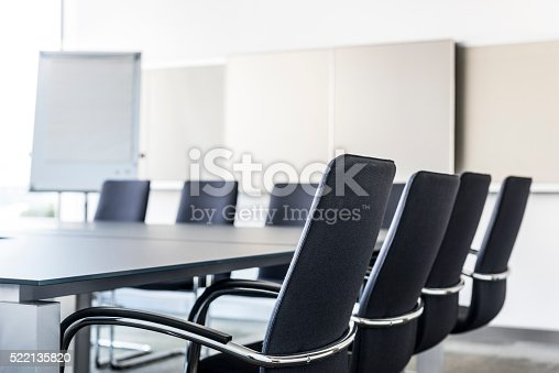 Abstract image of empty meeting room with table , chairs and flipchart board. Shallow depth of field, focus on foreground. Boardroom with focus on chair. Board room detail.