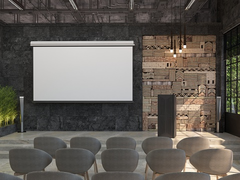 A meeting room with blank white screen for the projector on the black wall. The interior of the conference hall with a stage and a stand for performances.