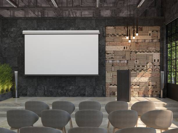 a meeting room with blank white screen for the projector on the black wall. the interior of the conference hall with a stage and a stand for performances. - stage performance space stock pictures, royalty-free photos & images