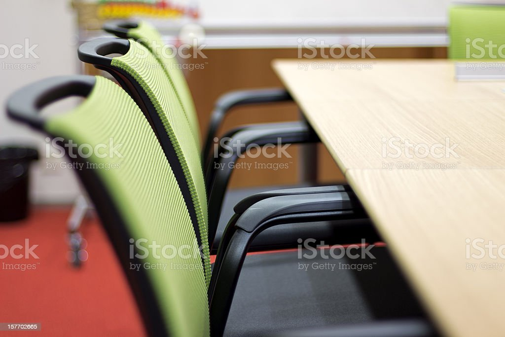 Meeting room with green chairs and wooden desk stock photo