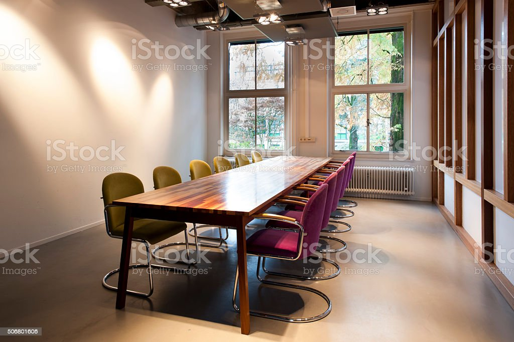 Meeting room with wooden table and 12 chairs stock photo