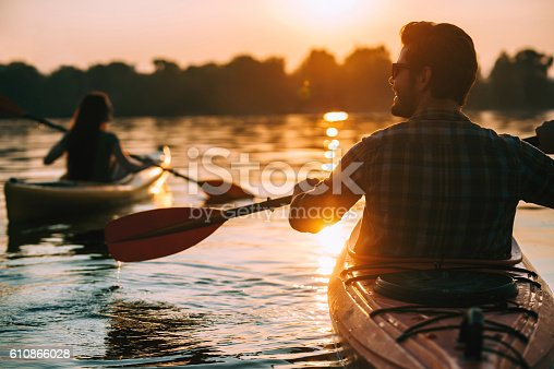 Rear view of young couple kayaking on lake together with sunset in the backgrounds