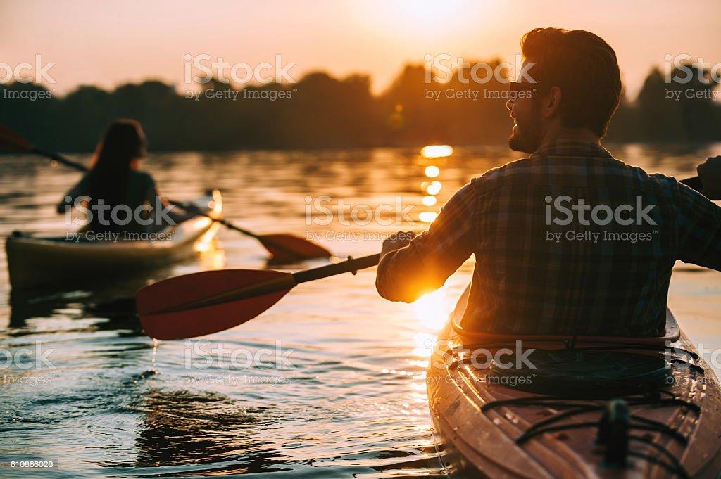 Meeting sunset on kayaks. stock photo