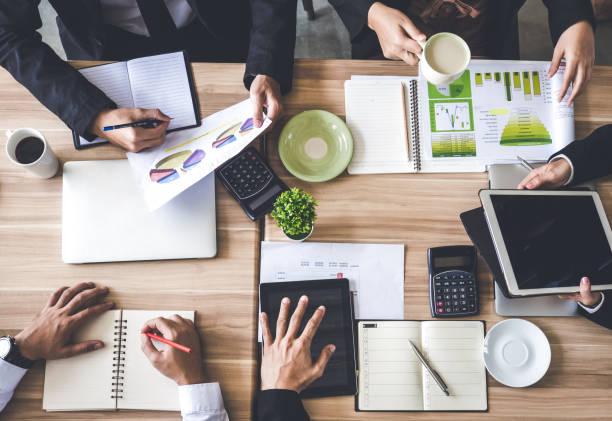 Vue de dessus du bureau/table de réunion, homme d'affaires, parler de plan d'affaires, rapport d'étape de travail de l'entreprise, rapport financier, statut, tablet, café, sur la table, en discutant avec une collègue au bureau - Photo