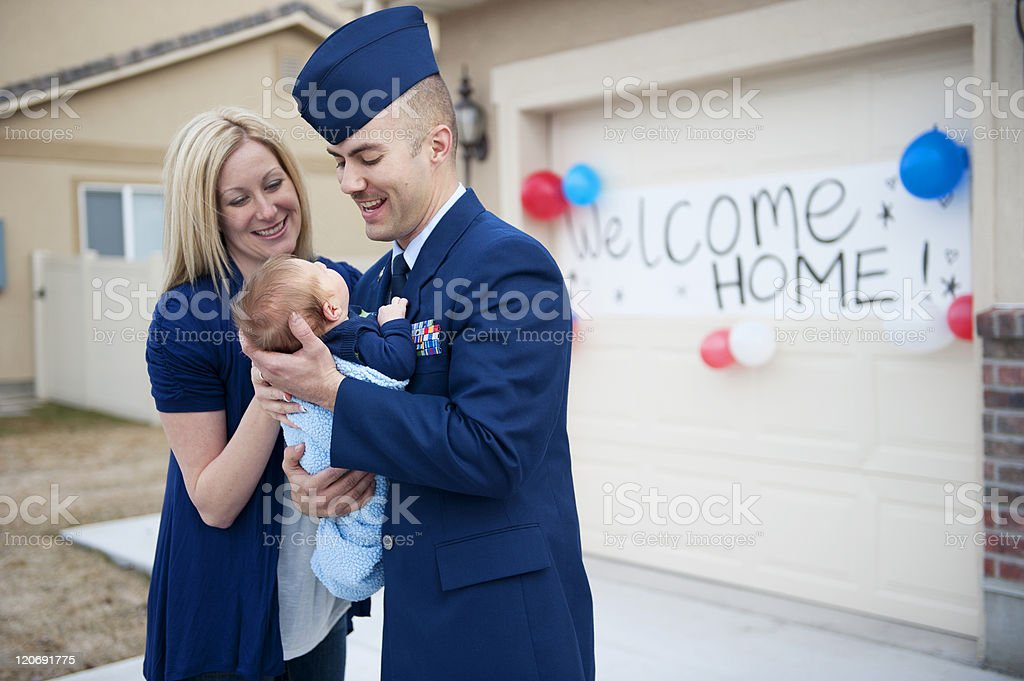 Meeting the baby An armed forces soldier is welcomed home by his wife and new baby.  0-11 Months Stock Photo
