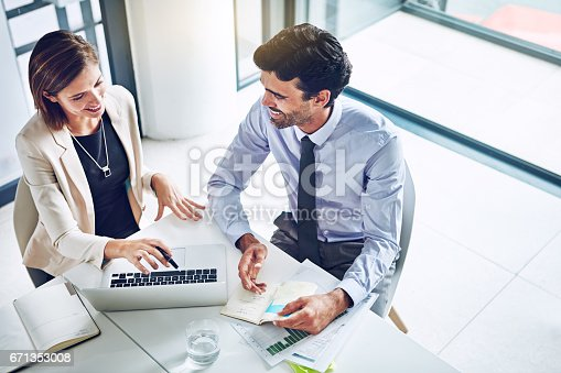 Cropped shot of two corporate businesspeople having a discussion in an office