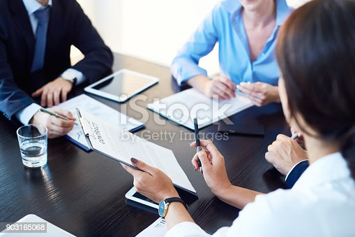 Unrecognizable business partners discussing agreement conditions reviewing it together at meeting