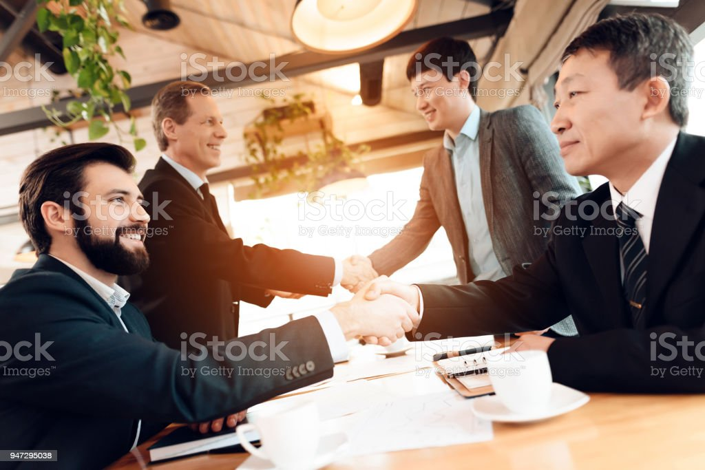 Meeting with chinese businessmen in restaurant. Men are shaking hands. stock photo