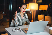 Shot of a young businesswoman using a laptop to make a conference call during a late night at work