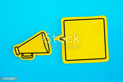 1192285342 istock photo Megaphone drawing on the cut yellow paper makes announcement with empty speech bubble. 1223408377