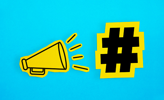 Megaphone Drawing On The Cut Yellow Paper Makes Hashtag Icon Announcement Stock Photo - Download Image Now