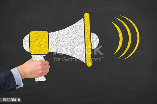 istock Megaphone In Human Hand on Blackboard Background 579225318