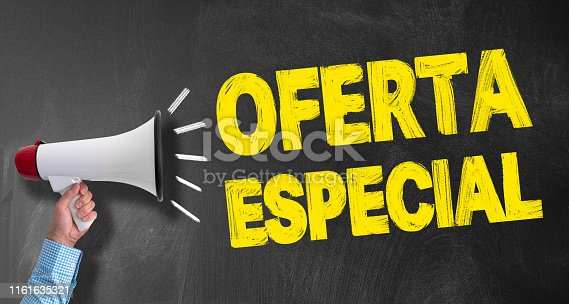 hand of businessman holding megaphone or bullhorn against blackboard with text OFERTA ESPECIAL, Spanish for SPECIAL OFFER