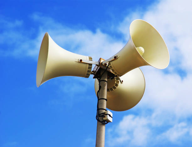 Megaphones for a public space. Three speakers attached to a mast on a background of blue sky. Amplification of sounds in all directions. onde sonore stock pictures, royalty-free photos & images