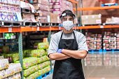Megastore young employee wearing a protective face mask and a face shield posing looking at the camera with his arms crossed
