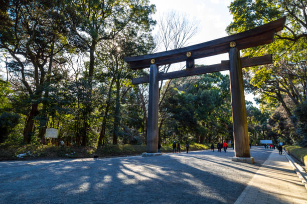 Meiji Shrine Meiji Shrine, Japan - 6th February, 2018. The Meiji Shrine can be found in the Shibuya district of Tokyo.  It is a beautiful and serene haven in the hectic city and its grounds and surrounding park cover a large area. Tourists and locals visit the shrine every day of the year and can be seen in the photo. shrine stock pictures, royalty-free photos & images