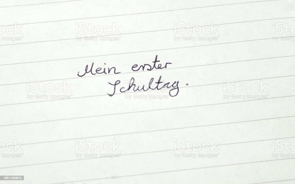 Mein erster Schultag (German: My first day at school) in handwriting on lined paper royalty-free stock photo