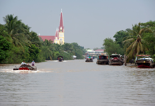Cai Thia area, Mekong Delta, South Vietnam. Water craft traffic such as barges, houseboats, passenger craft, industrial freighters and small personal boats travel the green rippled waters of the channels and routes of the mighty Mekong River as it flows to the Mekong Delta, South Vietnam