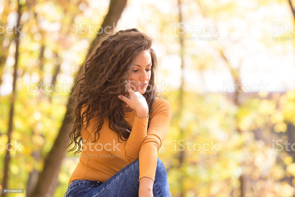 Melancholic cute curly girl sitting and thinking in forest on...