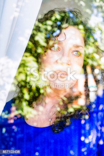 543048812 istock photo Melancholic mature Caucasian female looking out of a window with sad expression 857103438