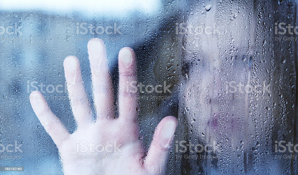 melancholy and sad young  woman  at the window in rain stock photo