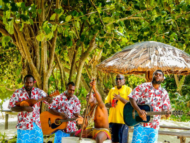 A Melanesian band plays music for tourists on the beach at Pele Island, a tiny island off the north coast of the island of Efate in Vanuatu stock photo