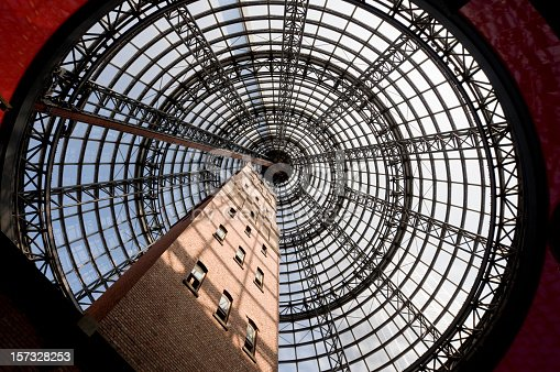An old factory chimney enclosed in a modern dome in a Melbourne shopping centre.