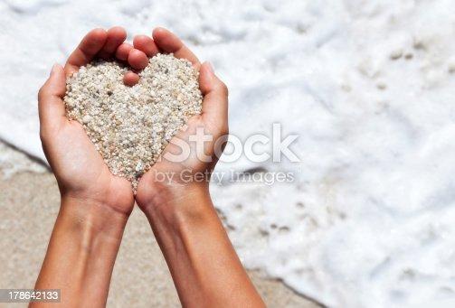 Mellow heart shaping female hands above beach