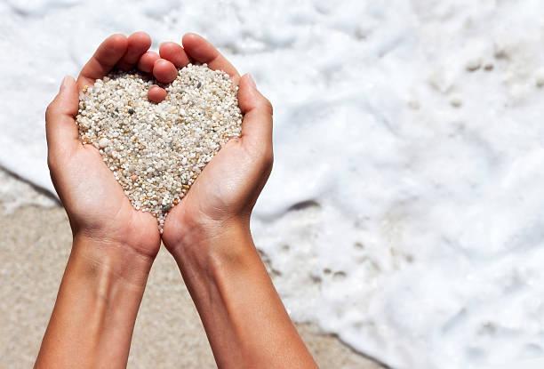 Warme Herz Formen weibliche Hände über dem Strand – Foto
