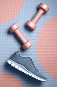 istock Mellow rose color dumbbells and Skyway color sneakers on the mat flat lay 1153876554