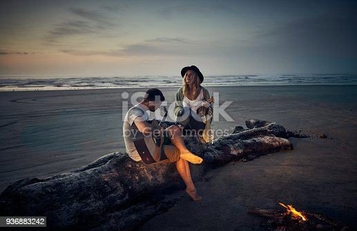 Shot of a young couple playing guitars together while camping along the coast