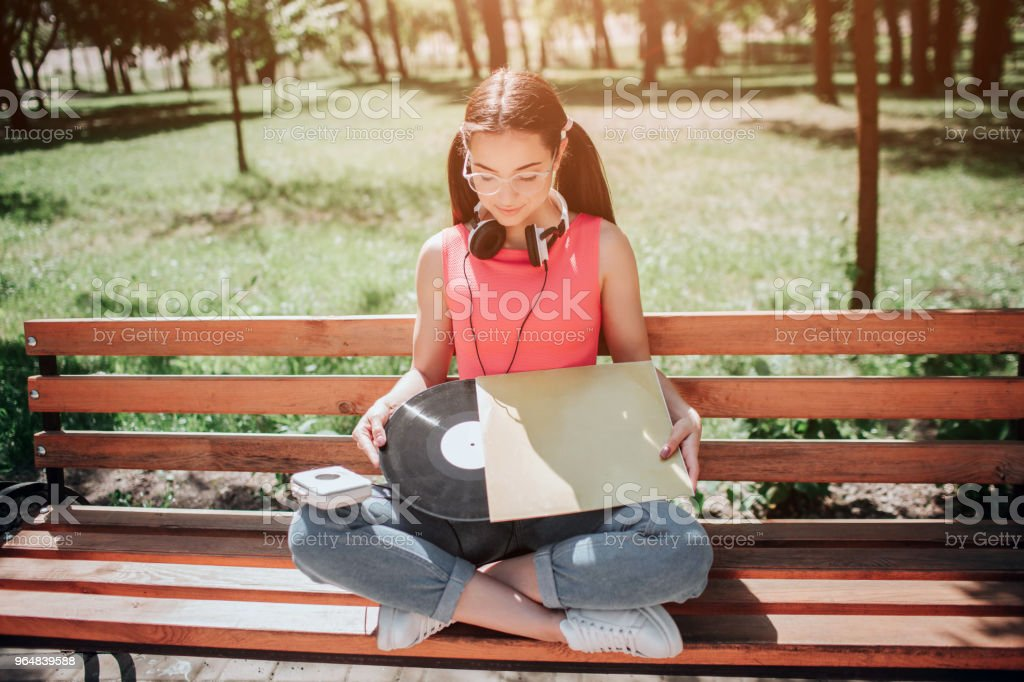 Melomaniac girl is holding a vynil and cover from it in her hands. She is looking at it. Girl is siiting on bench with her legs crossed royalty-free stock photo