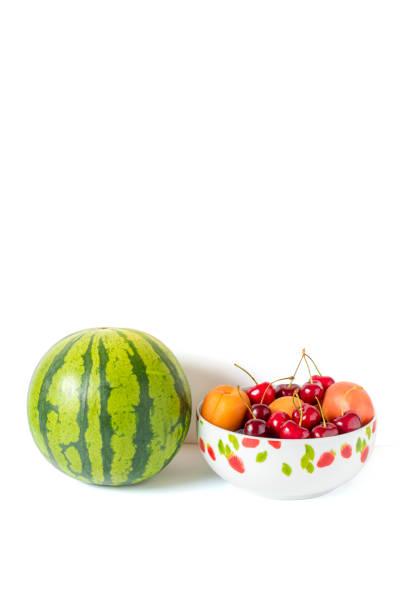 eine melone und eine obstschale mit kirschen und pfirsiche - essensrezepte stock-fotos und bilder