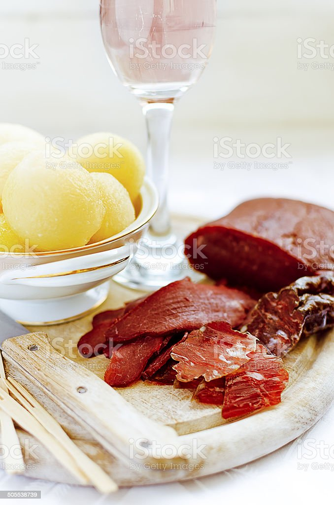 Melon balls with cured ostrich ham and sausage, blush wine stock photo