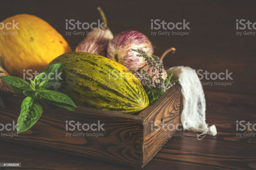 Melon, basil, mint, purple graffiti eggplants, onion and green fresh basil in a wooden box in a vintage wooden background in rustic style, selective focus, toned photo stock photo